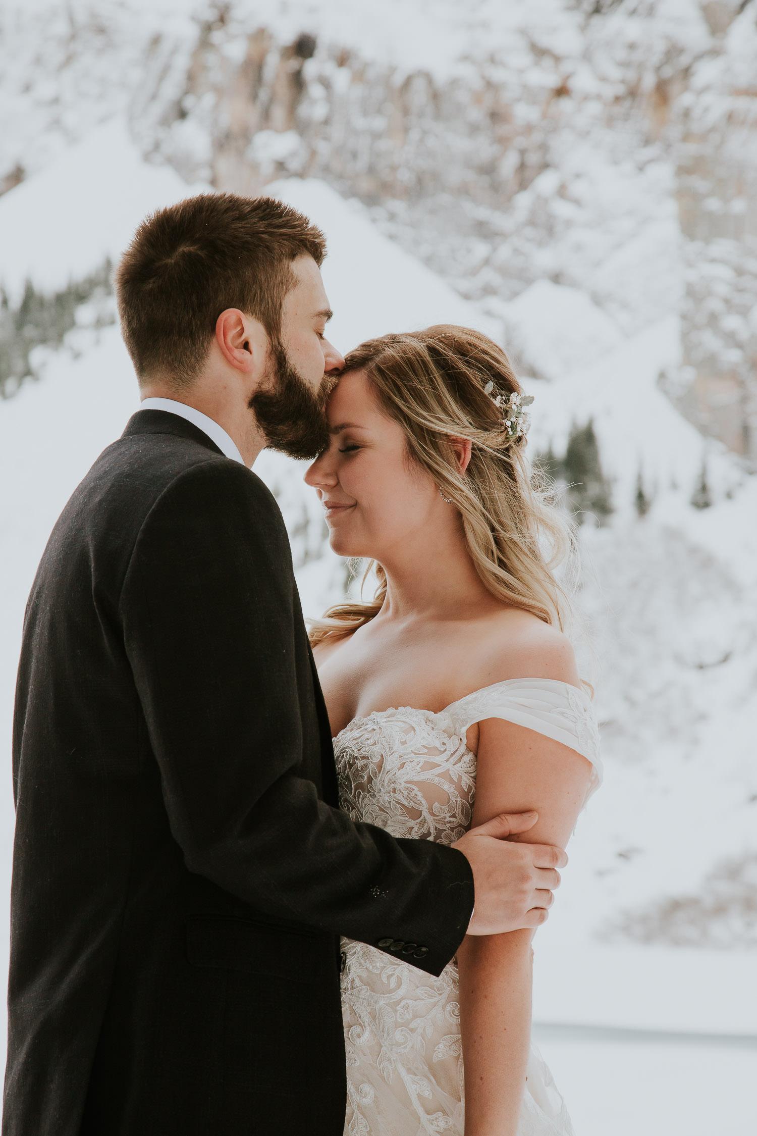 groom kissing bride in Canadian Rockys