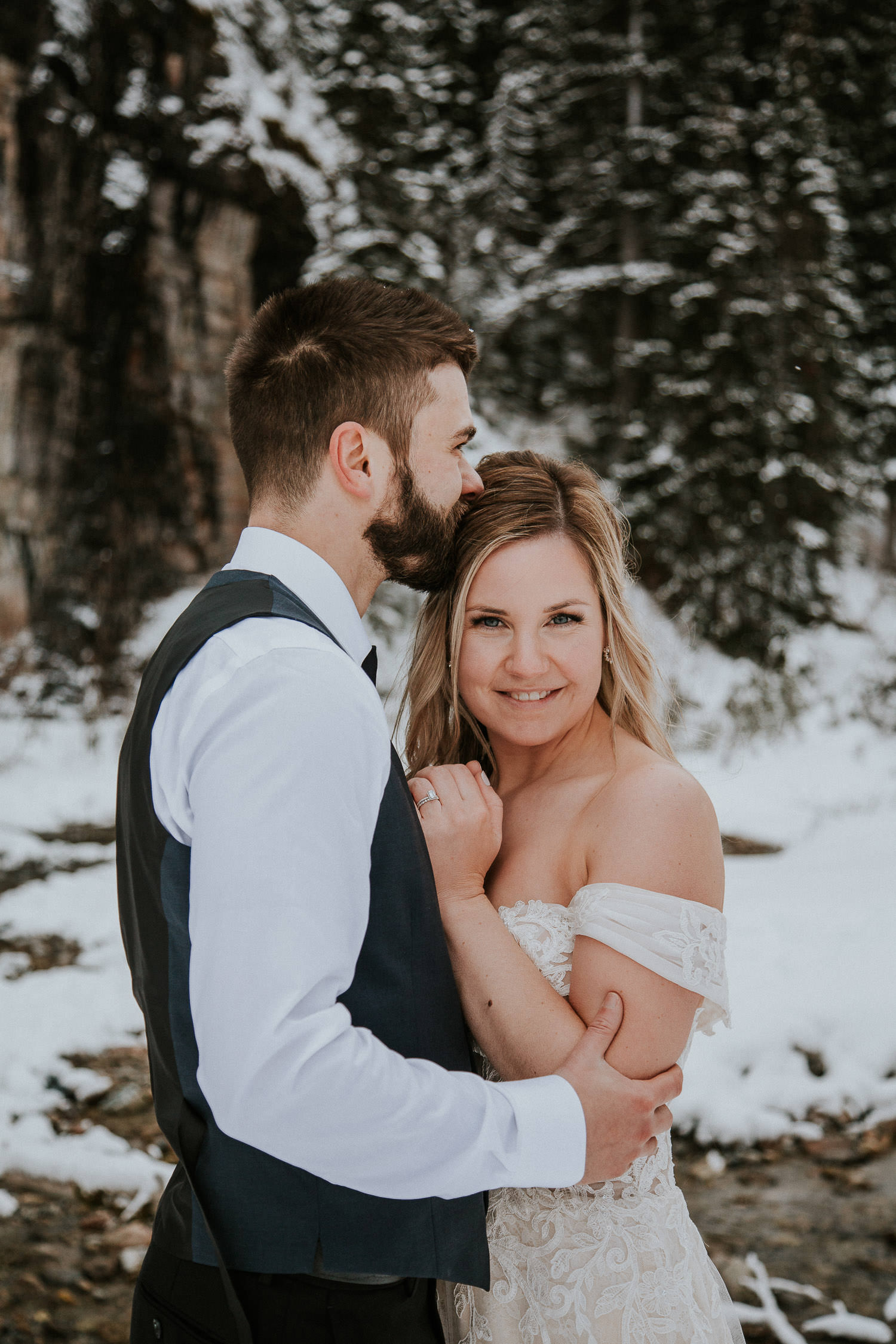 cold couple in Lake Louise cuddling on their wedding day