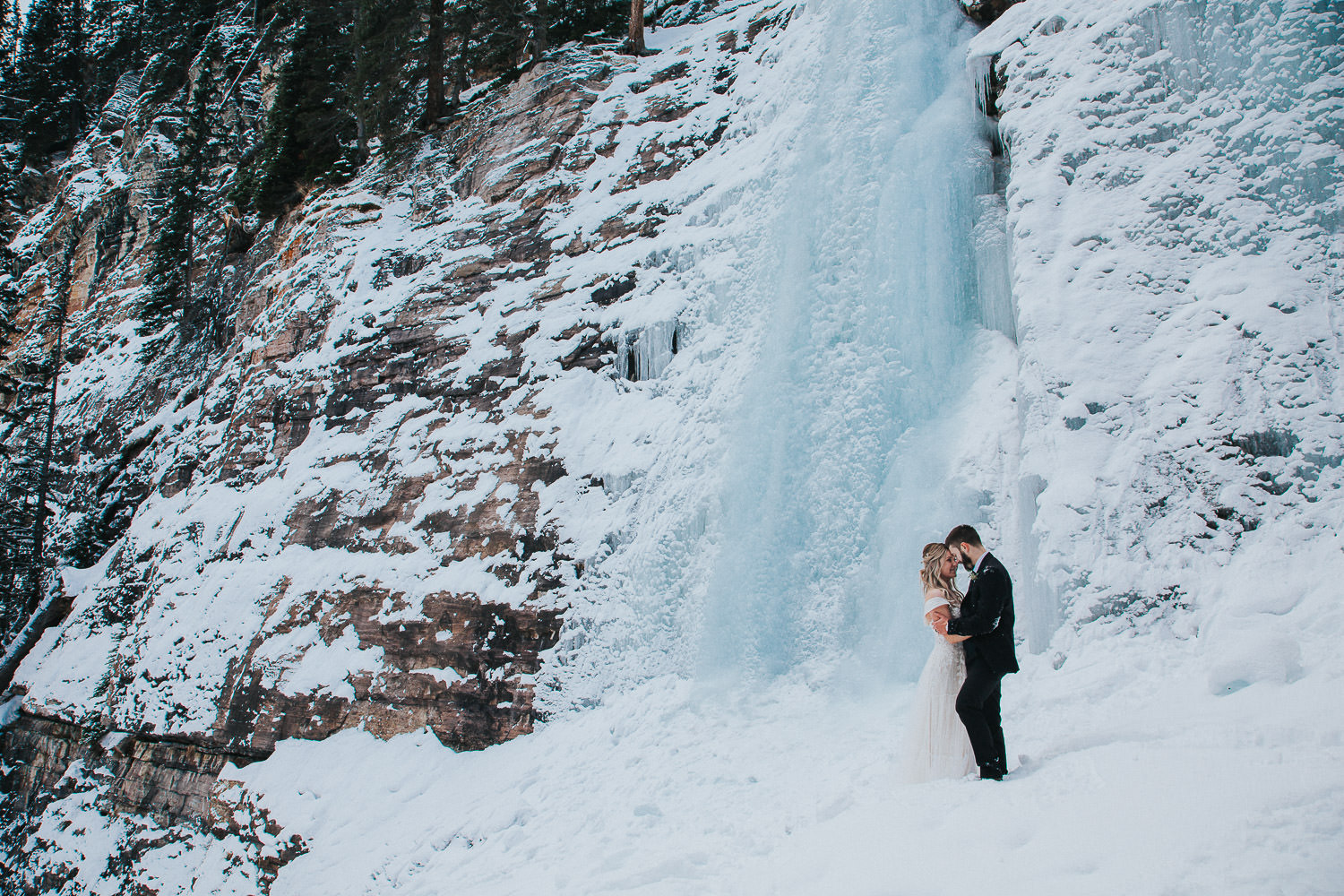 frozen waterfall bride and groom staying with it