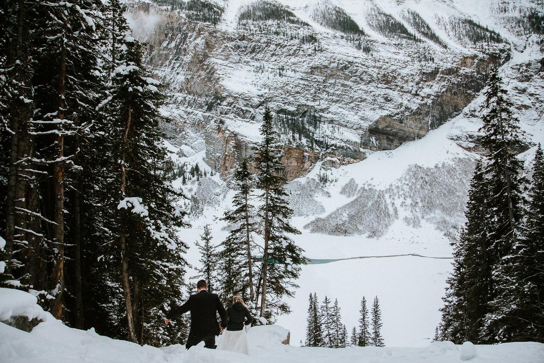 climbing down a mountain in wedding dress Lake Louise